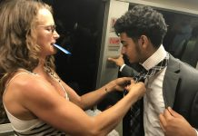 Fellow Passenger Helps Young Man With His Tie On Train